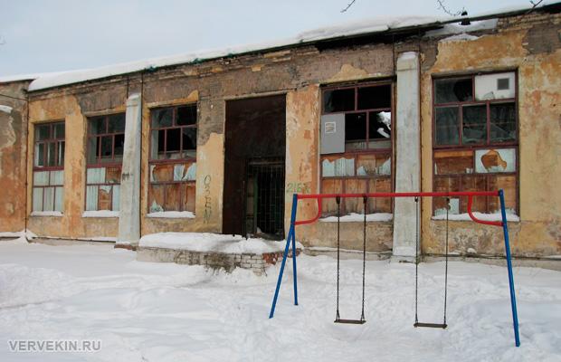 Детские качели на фоне руин